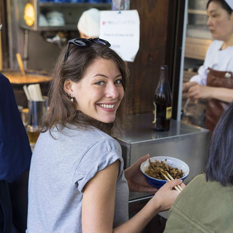 Sofia Levin looks over her shoulder at the camera while eating from a blue bowl with chopsticks. She is wearing a grey t-shirt and has a pair of sunglasses on her head.