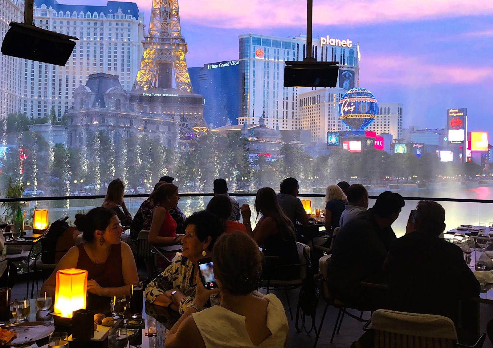 Diners sit in the dark at sunset as a fountain show goes on right outside the confines of their patio table. Celebrity chef restaurants in Las Vegas