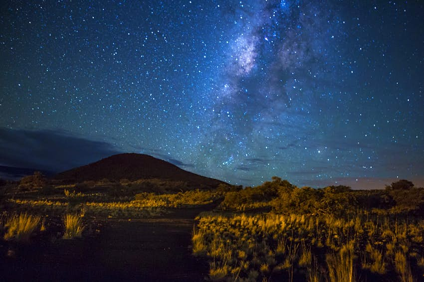 The dark sky is illuminated by millions of bright stars; in the background a mountain is shrouded in darkness; free things Hawaii