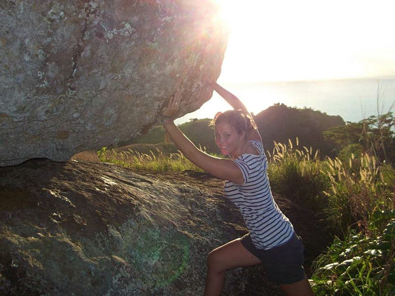 A smiling woman in a striped t-shirt and black shorts pushes against a huge boulder as the sun spills into the top of the frame.
