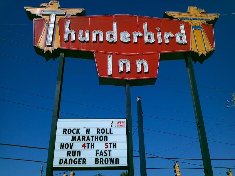 """A neon sign reading """"Thunderbird Inn,"""" with a blue sky behind"""