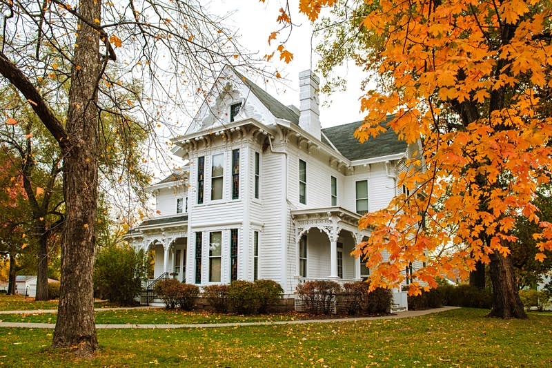 The white facade of the Truman House surrounded by orange leaves; historic homes