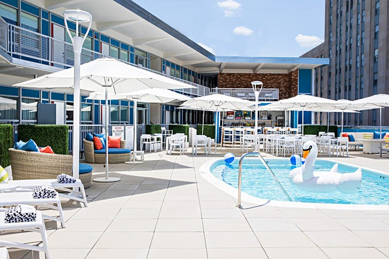 The pool area of Unscripted hotel, with a large inflatable swan and beach balls in the water and umbrellas surrounding