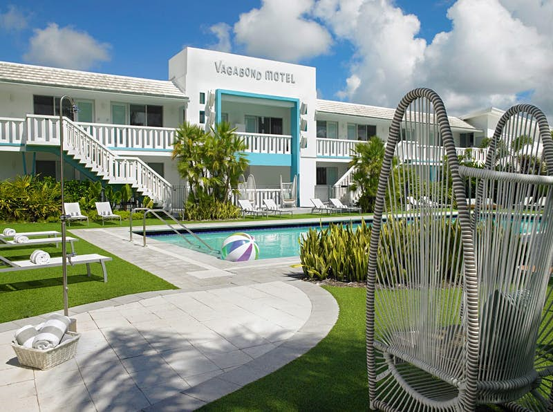 Exterior of Vagabond Motel and pool, with lounge chairs and green grass, coolest motels