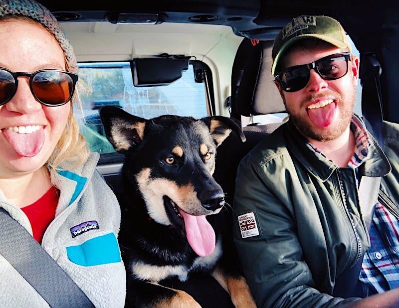 A man and a woman stick their tongues out in a selfie while riding in the cab of a truck as a dog in the back seat sticks its tongue out between them; travel with dogs