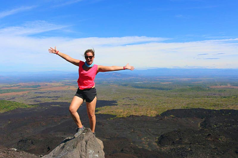 A woman stands on top of a volcano peak in trainers, black shorts and a pink sleeveless t-shirt with her arms outstretched. The Nicaraguan landscape spreads out far into the distance behind her and the blue sky is scattered with clouds.