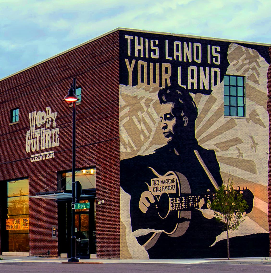 A large mural depicts Woody Guthrie and the phrase 'This land is your land' on the side of the center. USA museums for music lovers