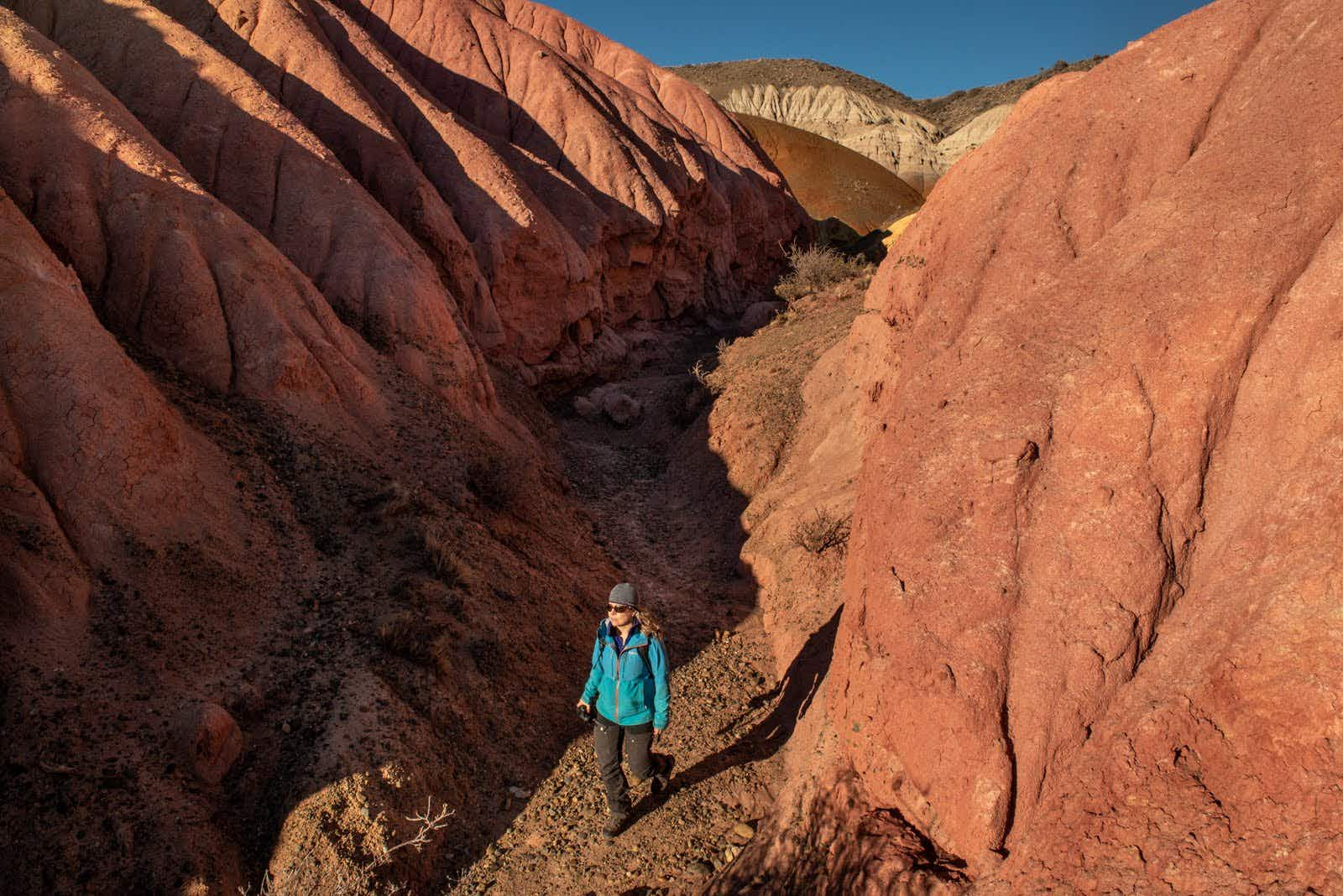 A hiker surrounded by a short canyon of red rock walls in Argentina's Patagonia National Park