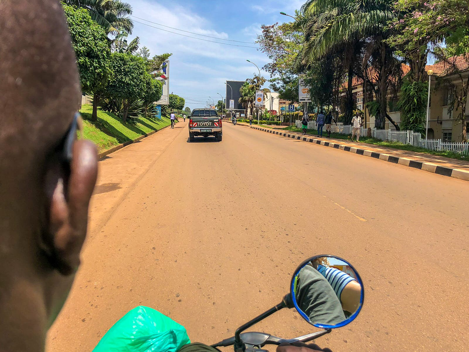 The right-hand side of the head of the motorcycle taxi (boda boda) driver is visible on the left side of the image; straight ahead is the sideview mirror and the paved road ahead