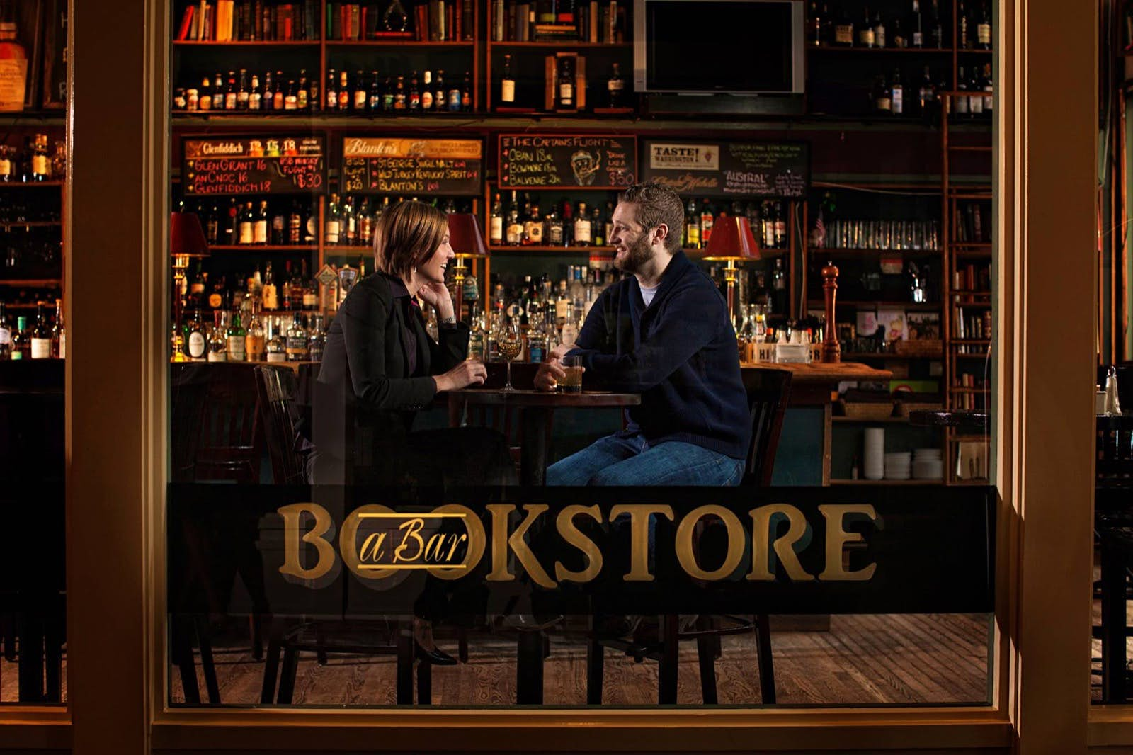 We see two people having drinks in a bar through the large front window, with the name Bookstore written on it. Perfect weekend in Seattle