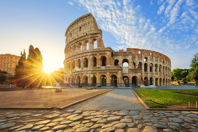 Looking over rough cobbles to a brilliant sun peaking over some distant trees, the Colosseum stands to the right in a golden light under a blue sky with cotton-like clouds above; an early start helps ensure a perfect weekend in Rome