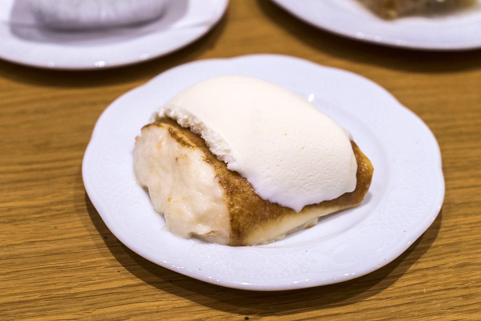 Tavuk göğsü in Turkey, a rice pudding-like dessert made from chicken. The dish is served on a white plate on a wooden table. Levin / Lonely Planet