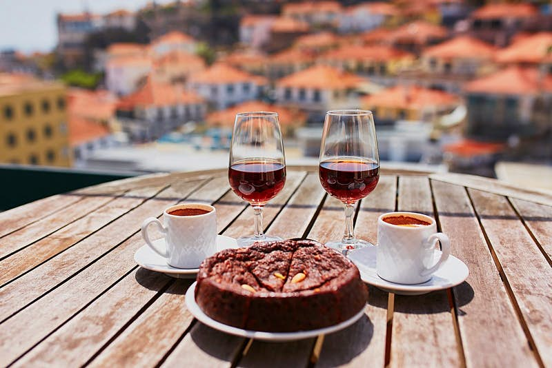 Two glasses of Madeira wine, two cups of espresso coffee and a traditional Portuguese honey and nut cake bolo de mel sit on a wooden tabletop with a view beyond of the blurred terracotta orange roofs of Funchal.