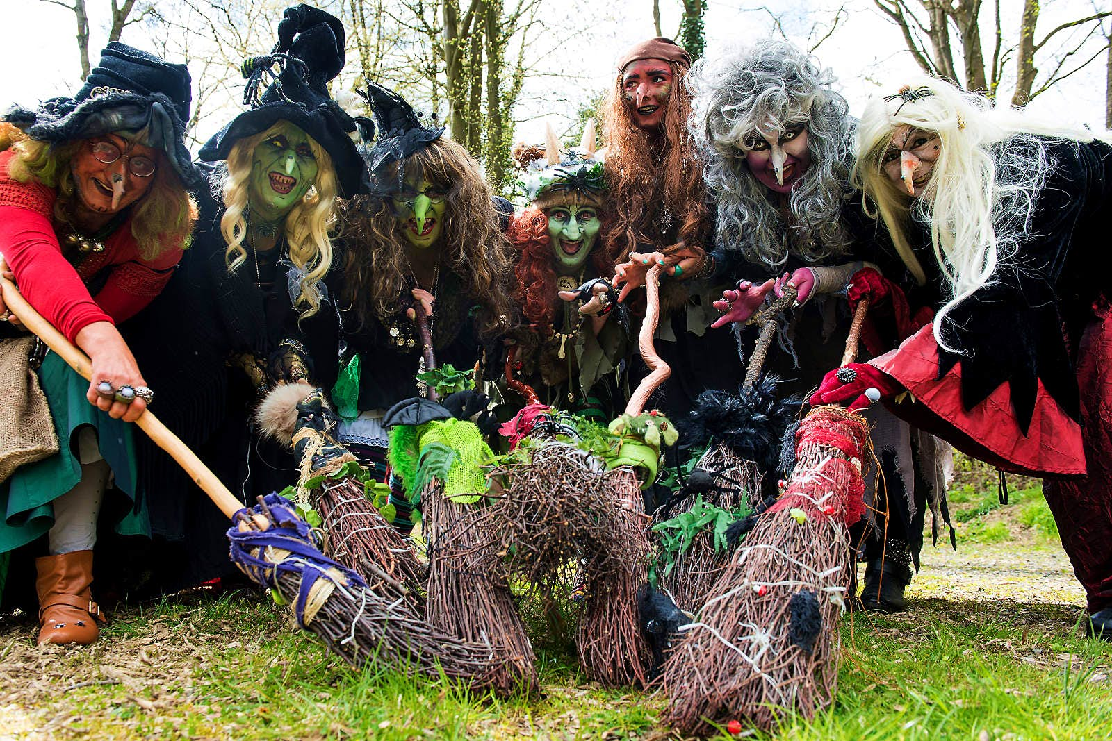 Seven women dressed in wigs and big hats, covered in face paint and fake noses and warts. They each hold a broom which they're pointing towards the camera.