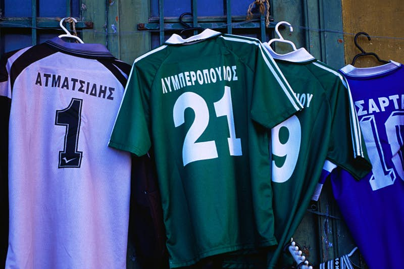 Four soccer shirts on hangers with Greek surnames emblazoned the back