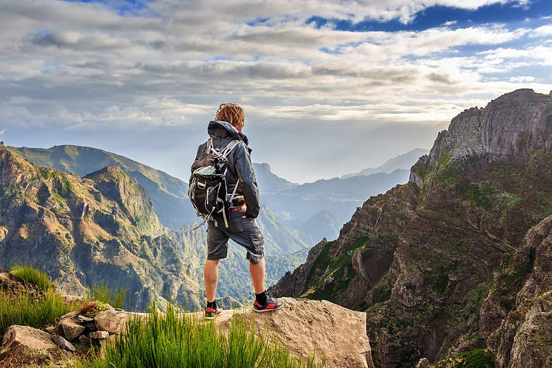 A hiker stands on a rocky ledge looking out over the rugged mountain scenery of the Pico do Arieiro in Madeira. They wear a waterproof jacket, back pack and shorts in shades of grey.
