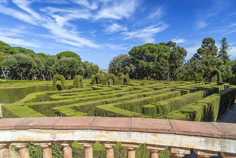 Looking over a pillared wall to a cypress hedge labyrinth below, with trees beyond.