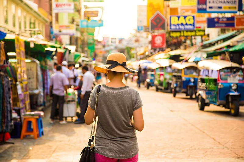 The back of a woman walking down a street in Bangkok lined with stalls and tuk tuks. She is wearing a grey tshirt and floppy cream-coloured hat.