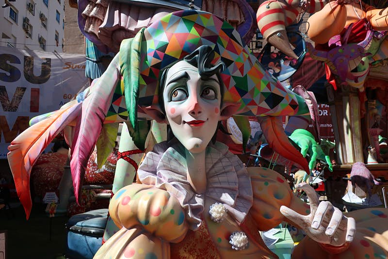 Close-up of a colourful falla sculpture of a clown wearing a large hat with feathers
