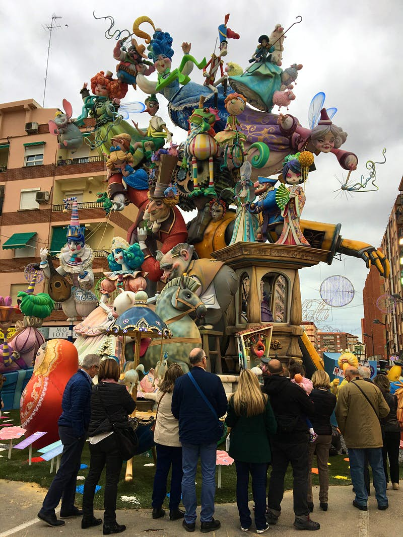 A group of people surrounding a tall falla monument and looking at the many colourful figures with a fairytale theme