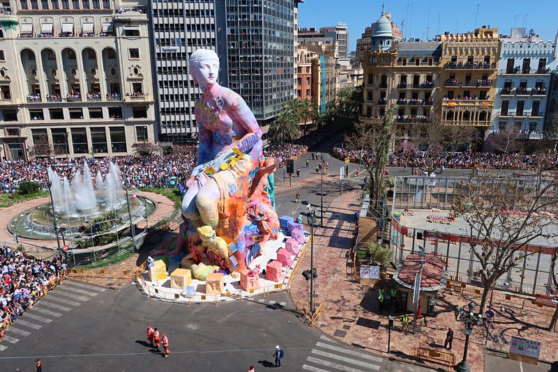 A massive, neoclassical-style sculpture of a woman, heavily covered in graffiti, stands in the middle of a large plaza, where crowds have gathered.