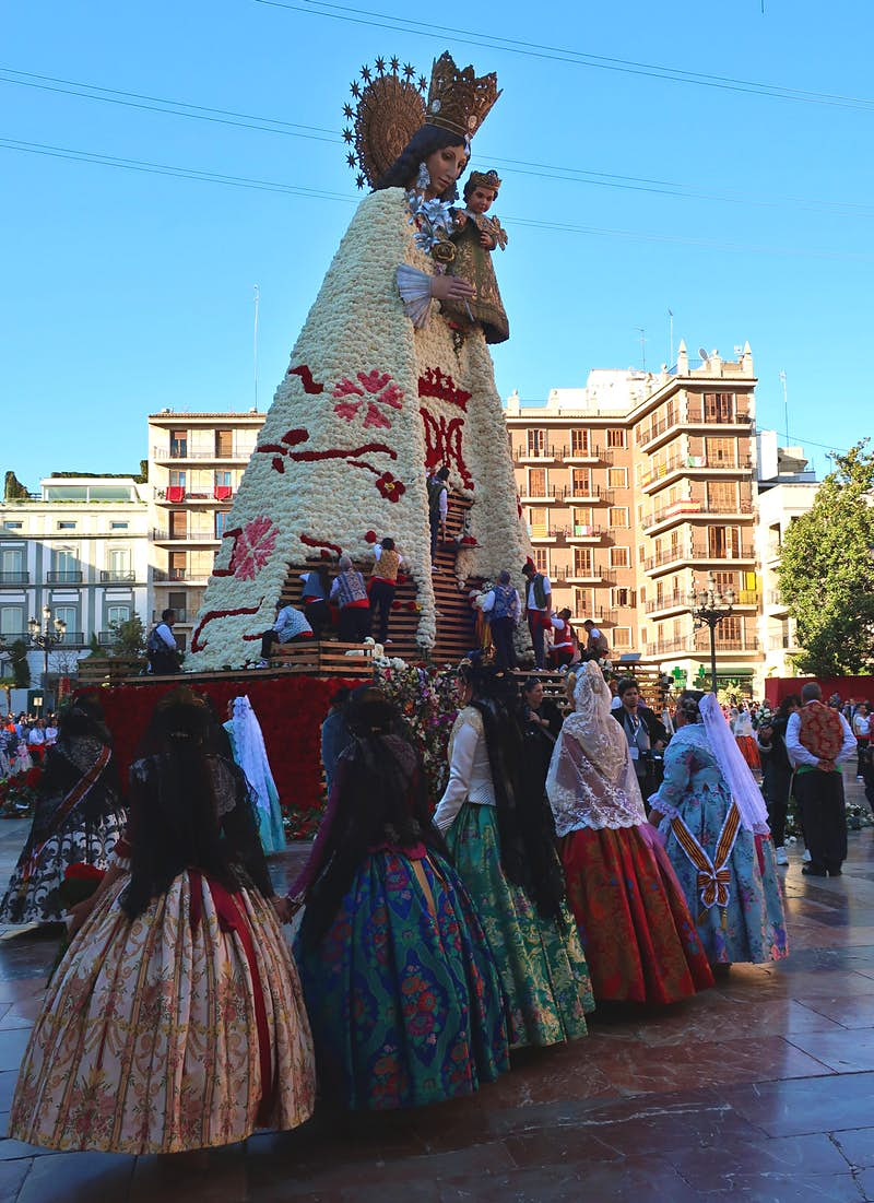 Five women in traditional dress look up at a wooden statue of the Virgin Mary, which is being decorated with bunches of flowers