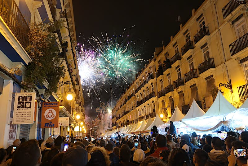 A crowd of people fill a street beneath tall buildings, while fireworks explode overhead.