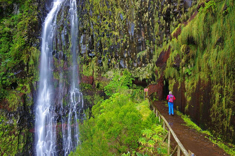 A woman stands by a levada, an open irrigation channel specific to Madeira, looking at a waterfall amid dense greenery and leafy scenery. She wears a colourful backpack, bright blue trousers and a purple gilet over a red long-sleeved top.