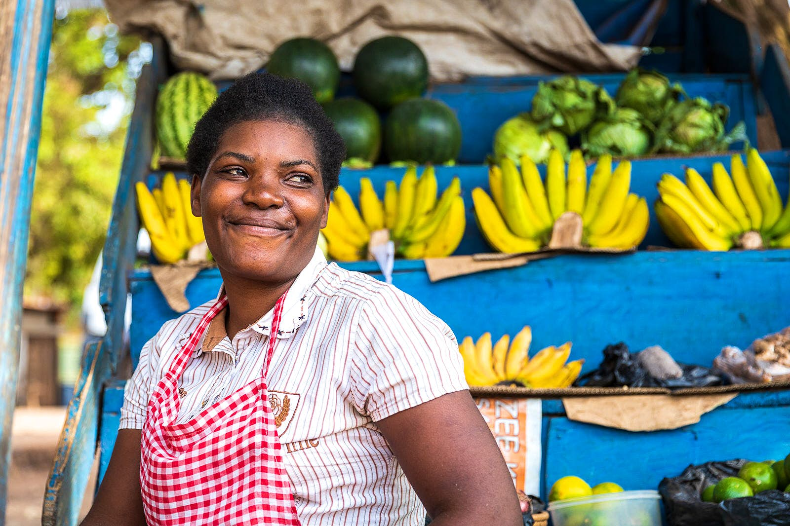 A Ugandan market trader grins, with rows of bananas stacked behind her