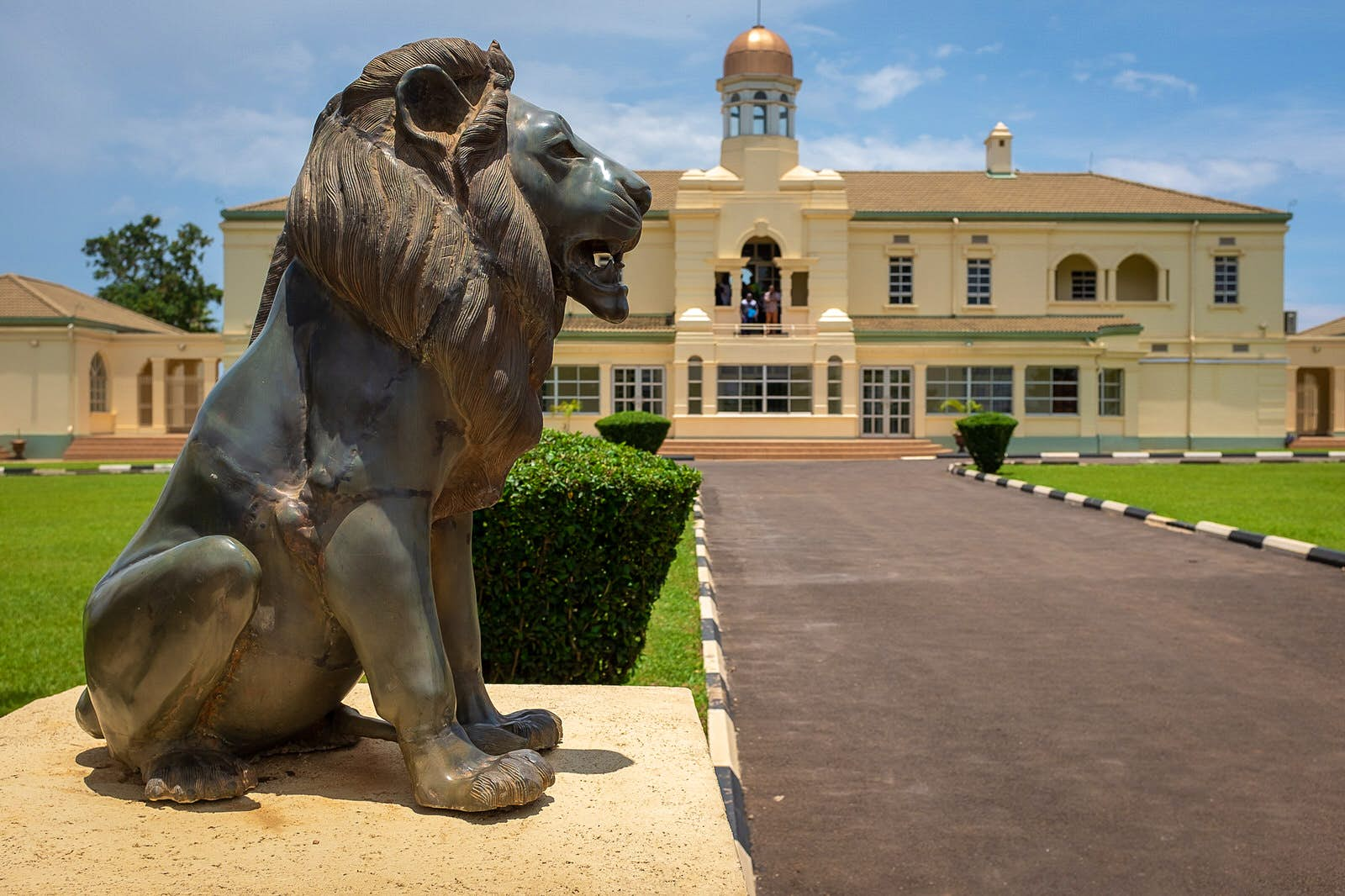 A large stone lion stands next to a paved path leading to Mengo Palace in the distance; the cream-coloured building is grand, with a gold-topped tower