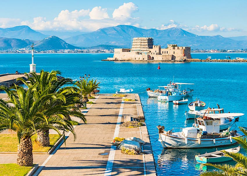 A paved jetty lined with palm trees, with boats next to it in the harbour; beyond is a fortress on an islet, with mountains on the coastline further away still.