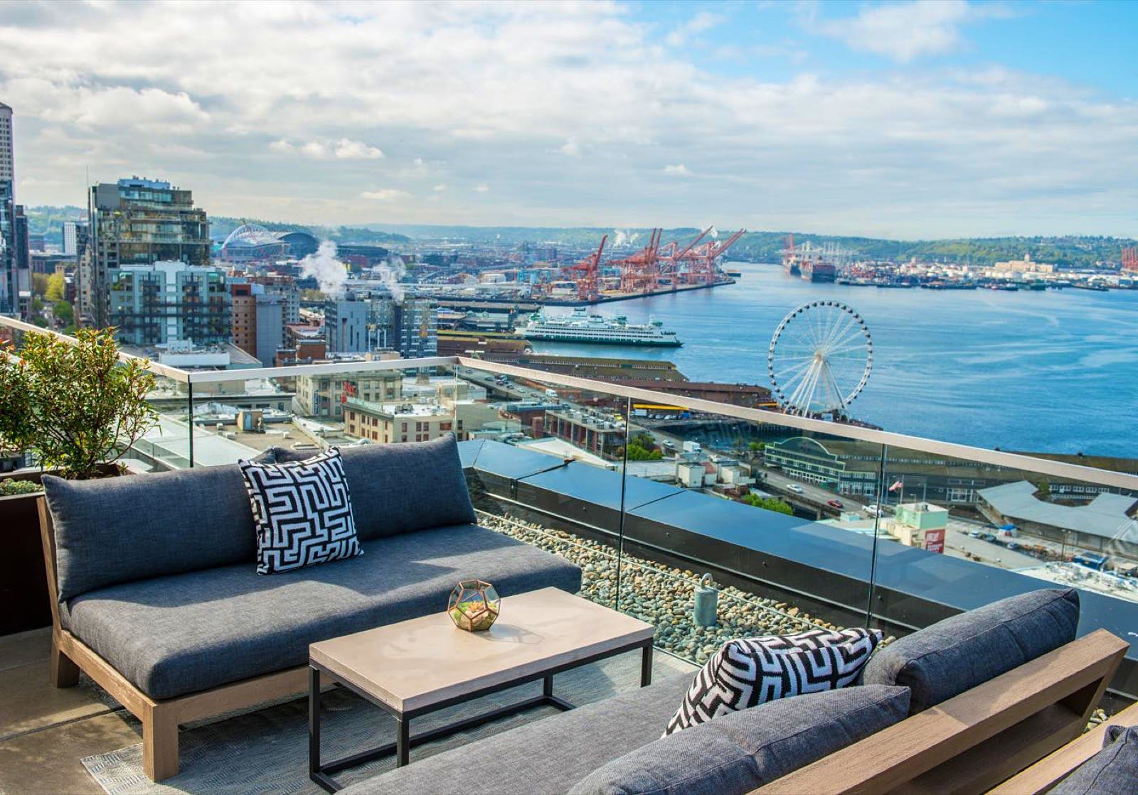 Modern couches and a coffee table are set up on a glass-walled, open air patio on top of a tall building on the Seattle waterfront. Perfect weekend in Seattle