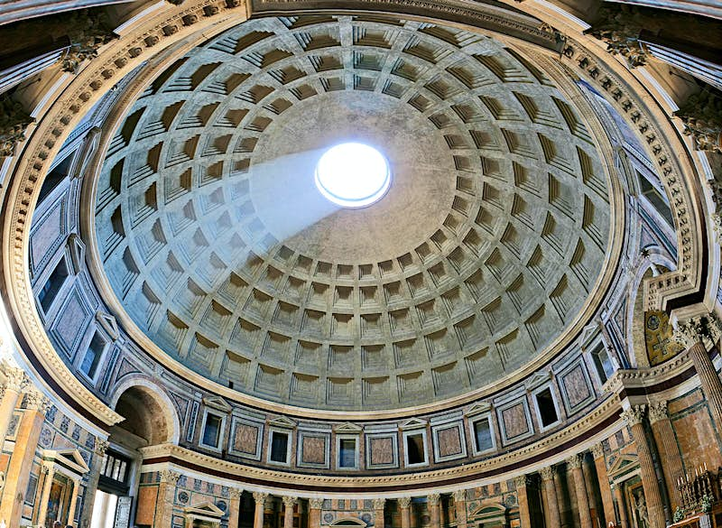 A beam of light breaks through the cirular hole atop the Pantheon's dome and cuts down into the building's interior