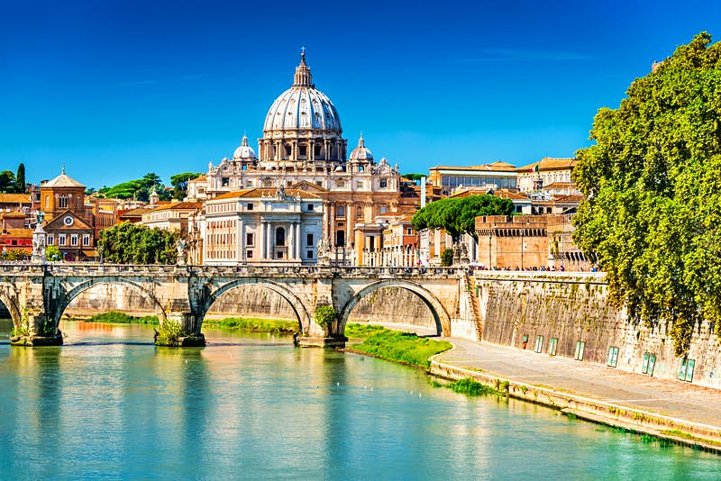 Under a brilliant blue sky the bridge of Pont Sant'Angelo crosses the calm blue waters of Tiber River from left to right, with St Peter's Basilica as a backdrop; no weekend in Rome could be complete without crossing this bridge