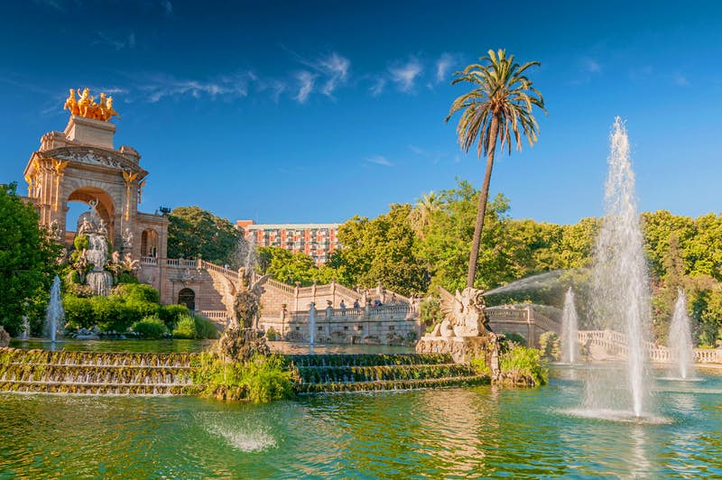 A large ornate stone fountain and pond on a sunny day in Barcelona.