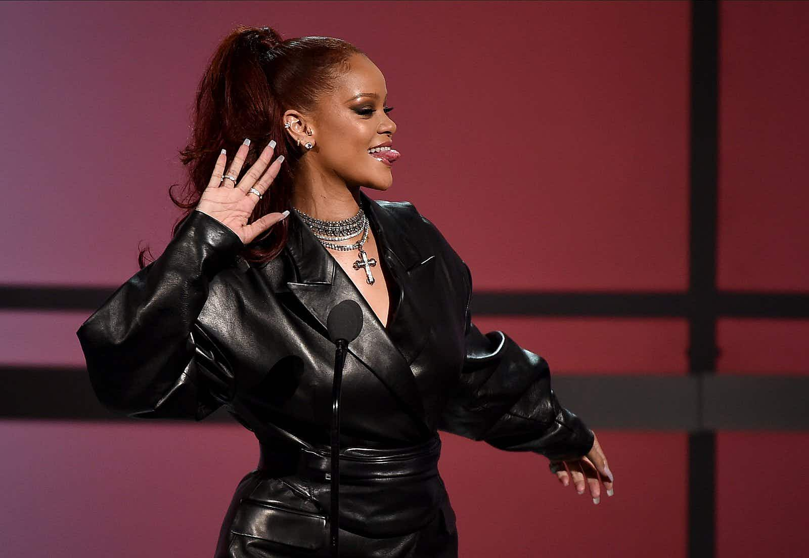Rihanna at the BET Awards Show at the Microsoft Theater in Los Angeles, USA on 23 June 2019; she wears a black leather coat, a sparkly silver necklace and is playfully sticking her tongue out.