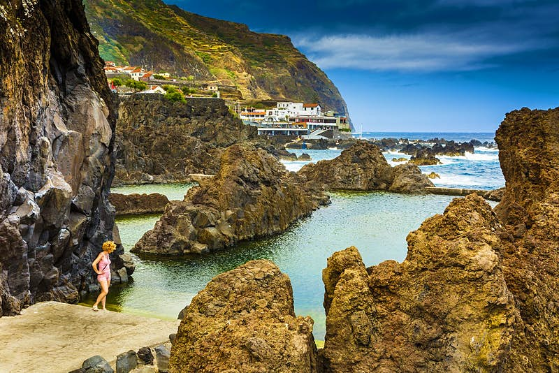 A woman wearing a pink vest and shorts stands at the edge of a natural pool made of volcanic rock next to the ocean; beyond is a village and tall cliffs.