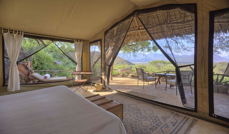 A luxury tent on a Kenyan field, with blue skies overhead; all-inclusive resort adventures
