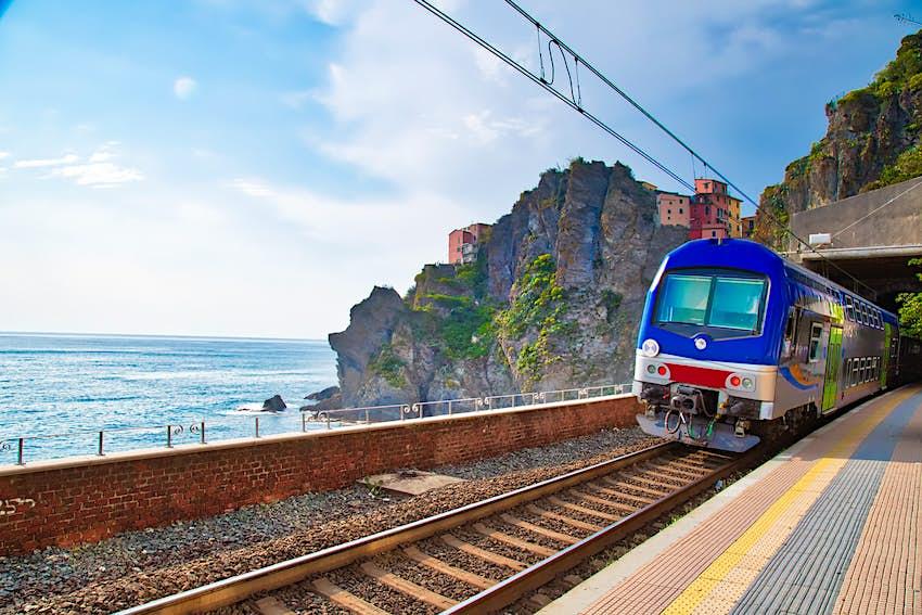 A blue train passes through Manarola Train Station in Italy