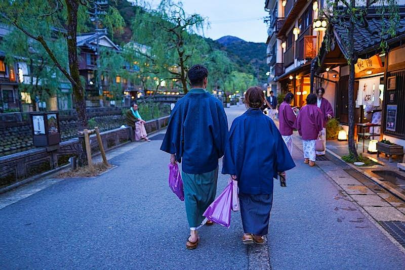 Cặp vợ chồng Nhật Bản mặc yukata (kimono thông thường) và đi bộ bên ngoài một onsen ở Kinosaki