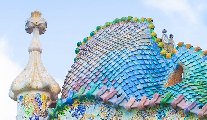 A close-up of shimmering tiles in blues, greens, pinks and yellows, creating an effect like fish scales or dragon skin