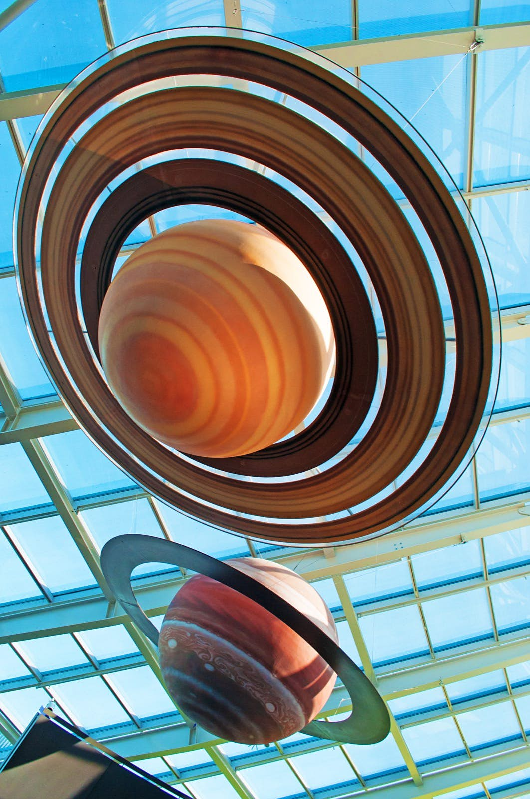 Reconstruction of the solar system at Adler Planetarium. The photos shows two ringed planets, one is orange and yellow with brown rings and the other is red and white with a green ring. The planets are suspended beneath a glass roof through which we can see a clear blue sky; Apollo anniversary experiences