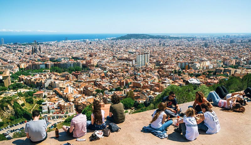 Teens sit on the viewpoint with a view of the city of Barcelona stretching off into the distance