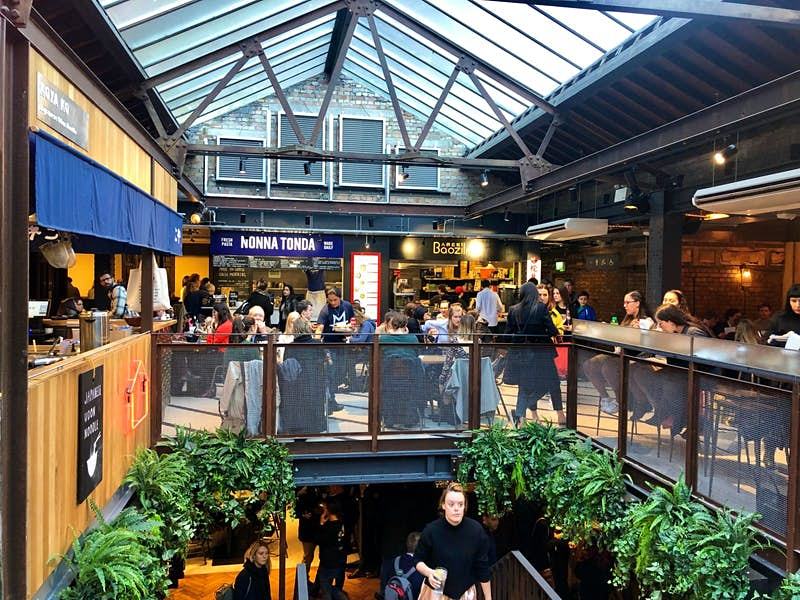 Several diners sit at tables below a glass roof in Victoria's Market Hall