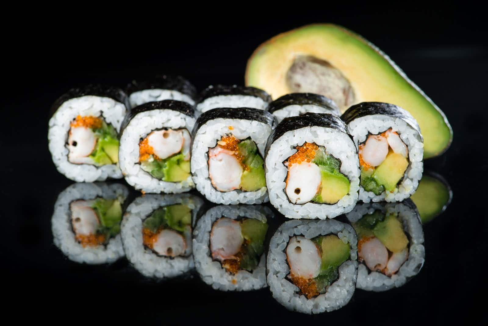Fresh delicious Japanese sushi with avocado, cucumber, shrimp and caviar on dark background