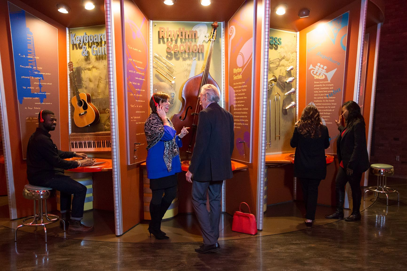 People stand listening to headphones inside the American Jazz Museum. USA museums for music lovers
