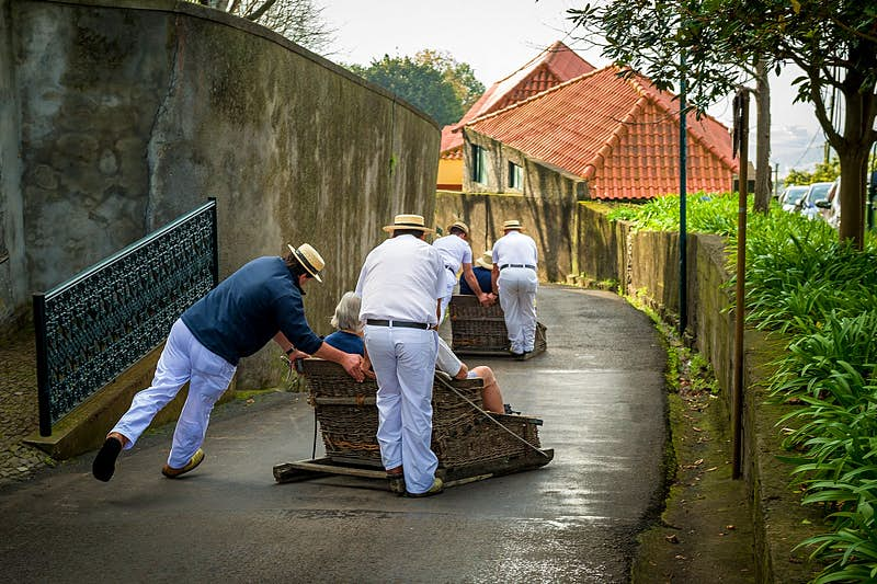 Men in white trousers and boater hats drive passengers in traditional wicker sledges downhill on the streets of Funchal.; it's one of the most fun things to do in Madeira.