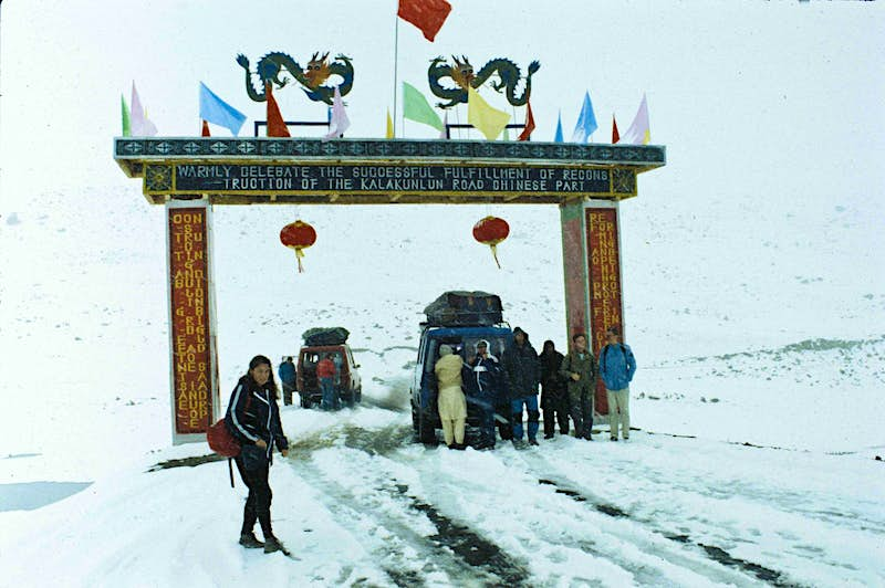 A woman stands in front of the Khunjerab Pass. An ornately decorated entrance straddles the snow-covered road. Two cars are behind her, one stopped under the entrance and one just the far side of it. People are standing around both vehicles in heavy clothing.