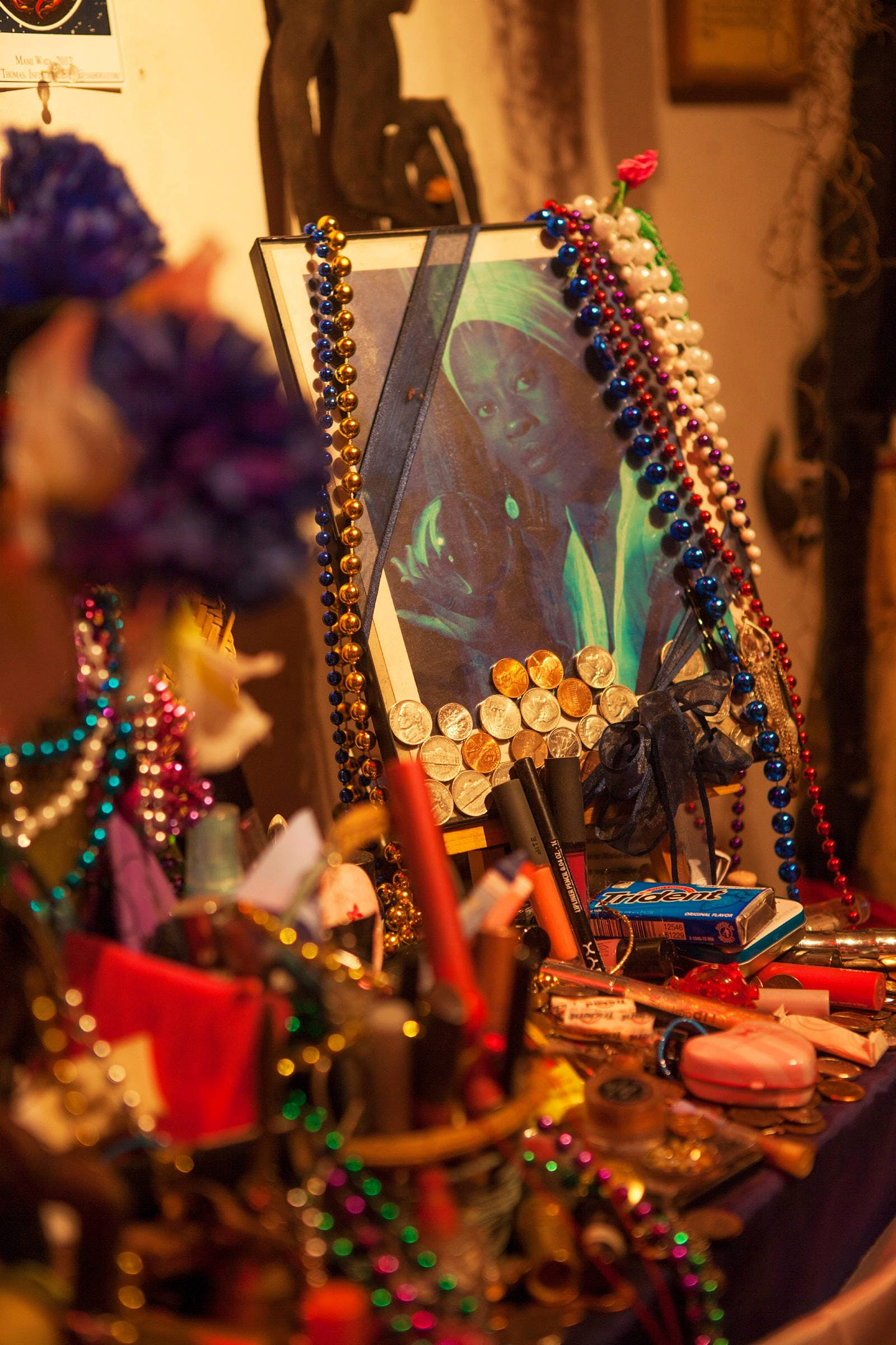 A framed picture stands in the middle of an altar with a photo of a woman with long fingernails in a white turban, clothes and earrings holding a crystal ball. Strings of beads surround it, along with coins, gum packets, pens and a heart-shaped box.