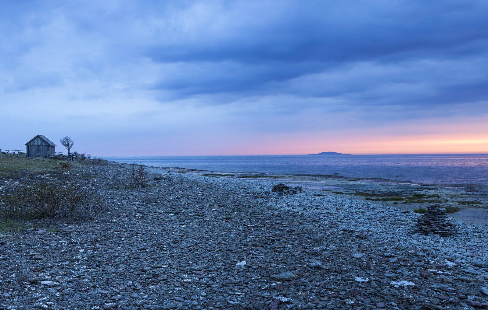 A stony beach after sunset with a sliver of pink in the sky. On the left background is an old timber hut with one bare tree next to it.